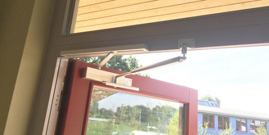 Amortisseur-limiteur d'ouverture avec ferme-portes dans une école
